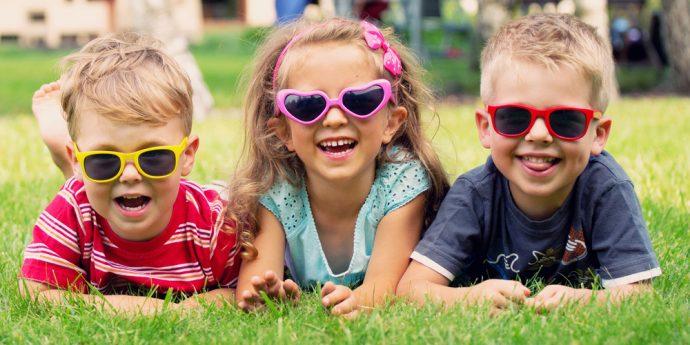 três crianças sorridentes de óculos escuros