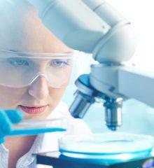 mulher cientista analisa substancias em um microscopio